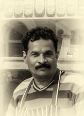 Minding the shop (David Feuerhelm) Tags: portrait monochrome nikkor man face shopkeeper street cambridge millroad nikon d750 sepia 2470mmf28