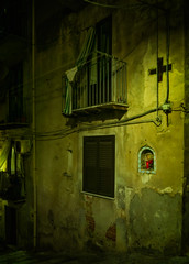 A street shrine, or tabernacle (Tigra K) Tags: cefalù palermo italy it 2018 architdetail balcony cefalu cross lattice laundry light medieval night painting religious ruin sicily texture town wall arch