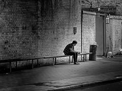 music against street noise (heinzkren) Tags: london gb uk street streetphotography city blackandwhite schwarzweis bw sw monochrome urban wall bricks long man mann bank bench solo milieu mood waiting station mauer ziegel ziegelmauer unterführung pause break panasonic lumix