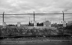 R1-068-32A (David Swift Photography) Tags: davidswiftphotography philadelphia southphilly chainlinkfence barbedwire signs emptylots noparking 35mm olympusstylusepic ilfordxp2 film