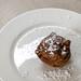 Niederländische Spezialität Oliebol mit Puderzucker bestäubt auf weißem Teller