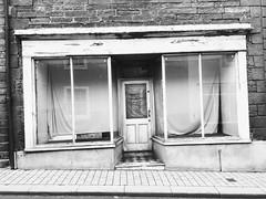 Old shop front in Penrith. (Bennydorm) Tags: vacant rundown urban business dingy town street pavement inglaterra inghilterra angleterre europe uk gb britain england cumbria penrith iphone6s iphone mono sad forlorn closed shut empty windows shopfront shop building