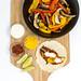 Vegetarische Fajita mit Paprika und Pilzen, gewürzt mit scharfer Tomatensoße und Limettenschmand auf einem Holzbrett mit einer schwarzen Schale auf einem Holzbrett in der Aufsicht auf weißem Hintergrund