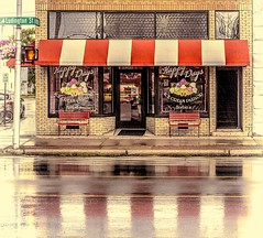 Herbie's Happy Days Ice Cream Parlor (Wes Iversen) Tags: escanaba hss herbieshappydaysicecreamparlor michigan sliderssunday up upperpeninsula awnings bench benches brick doors facade icecream icecreamparlors rain reflections retail streetsigns streets vacations water windows vintage