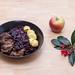 Rindergulasch nach traditioneller Art mit Apfelrotkohl und Miniknödel mit einem Zweig un einem Apfel auf einem Holztisch