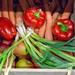 Frühlingszwiebeln, rote Paprika und Karotten in einer Holzkiste