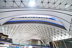 Hong Kong International Airport Gates 3 (ArdieBeaPhotography) Tags: airport gates travellator conveyorbelt rowsofchairs chairs seats clean white glow geometric pattern ceiling arched arcs triangular blue carpet passengers waiting windows night light bright flourescent wideangle