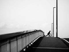 Lines... (明遊快) Tags: street bridge city cityscape highrise skyline monochrome bike man japanese pole lines road bw sky clouds