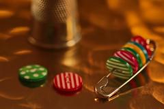 Safety pin and thimble (eleni m) Tags: macromondays safety hmm pin safetypin thimble buttons dof bokeh reflection small mini