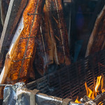 Herstellung von Flammlachs - Fischhälften hängen über offenem Feuer am Neumarkt in Köln thumbnail