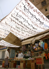 Small Shop Under A White Awning With Arabic Writing, Tarim Market, Yemen (Eric Lafforgue) Tags: arabia arabiafelix arabianpeninsula ball box colourpicture day economy fulllength hadhramaut hadhramawt hadhramout hadramaout hadramawt man market merchant placeofinterest realpeople selling shade shop tarim vertical writing yemen yemeni 0096yemenlafforgue