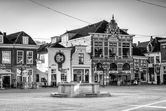 Corner of the Hof square (Dannis van der Heiden) Tags: fountain building historic brick square streetscene amersfoort netherlands blackandwhite blackwhite monochrome cafe bike scooter terras nikond750 d750 tamron70210mmf4 person walking reflection